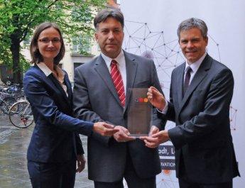 """Katrin Hennig (Initiative """"Land der Ideen"""") und Stefan Schellhorn (Deutsche Bank, rechts) überreichen Eric Hilgendorf die Auszeichnung für die Forschungsstelle RobotRecht. (Foto: Robert Emmerich)"""