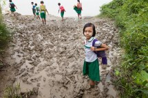 Girl Walking to School in the Mud Image