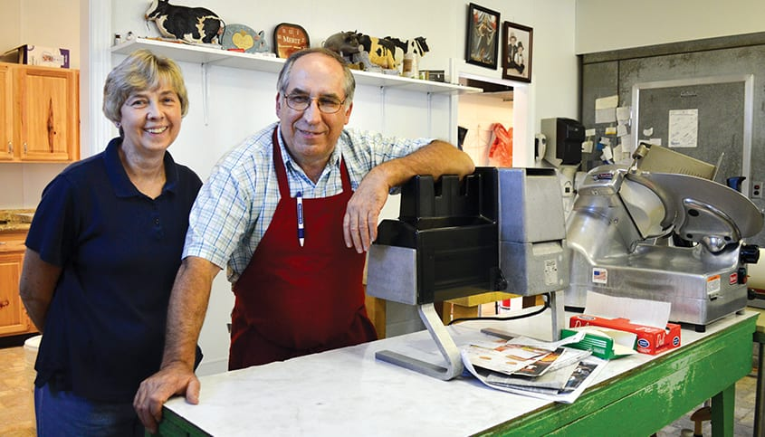 Ralph and Janet Richmond standing near a meet slicer