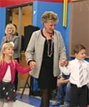 Gayle Manchin holding hands with two children