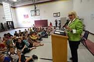 Joanne Tomblin addressing a room full of children.
