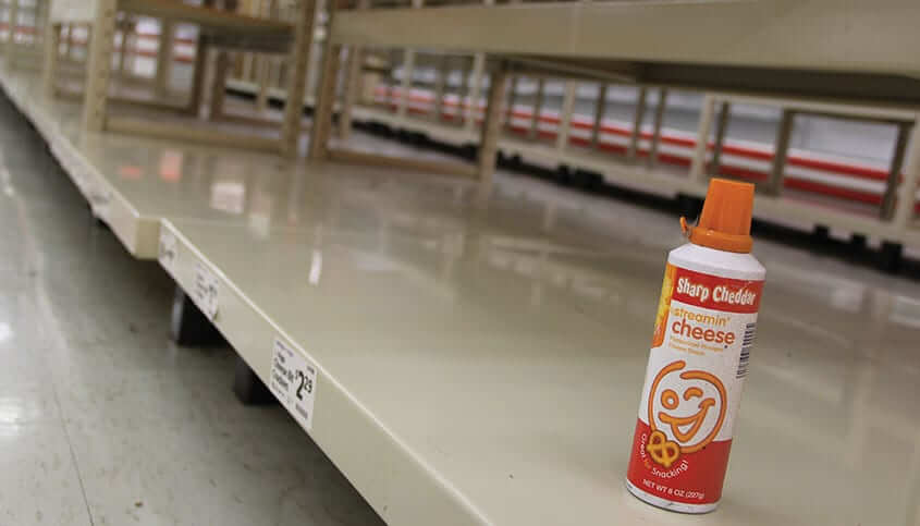 a lone spray can cheese container on the store's empty shelves
