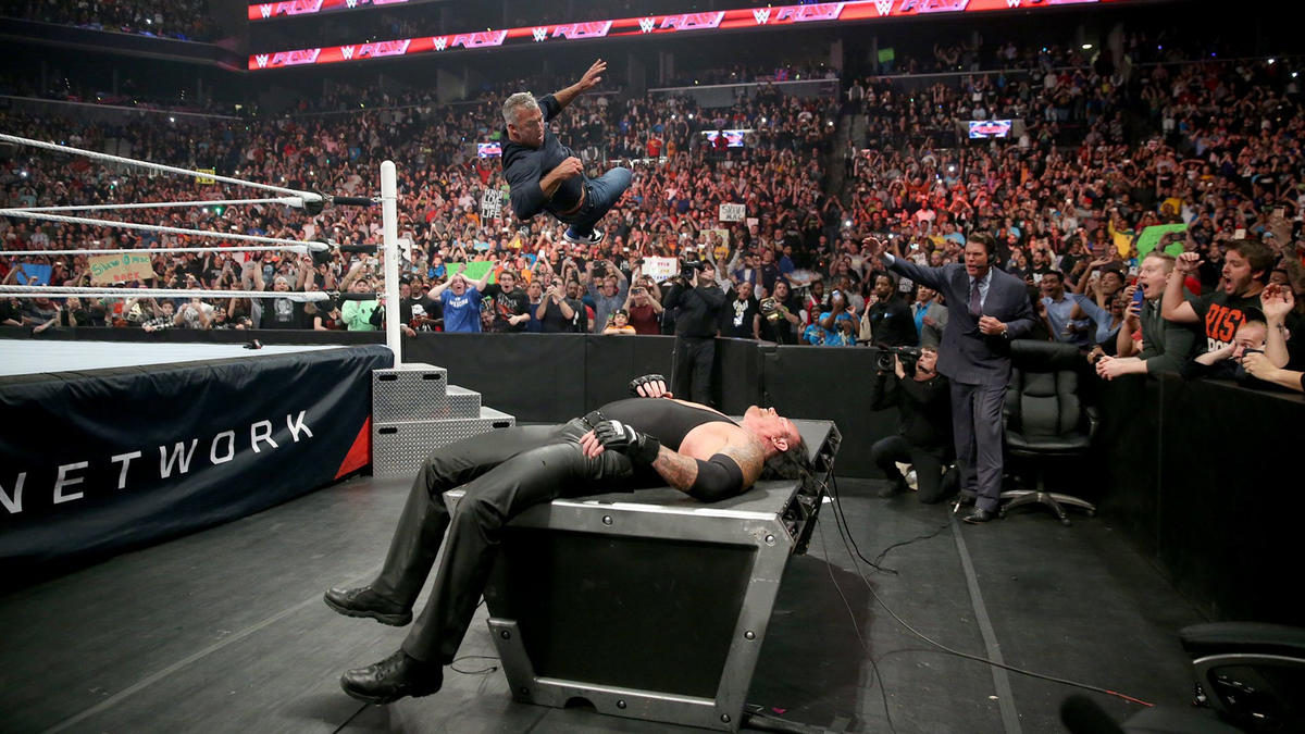 Shane throws caution to the wind and soars through the air, sending Undertaker crashing through the announce table.
