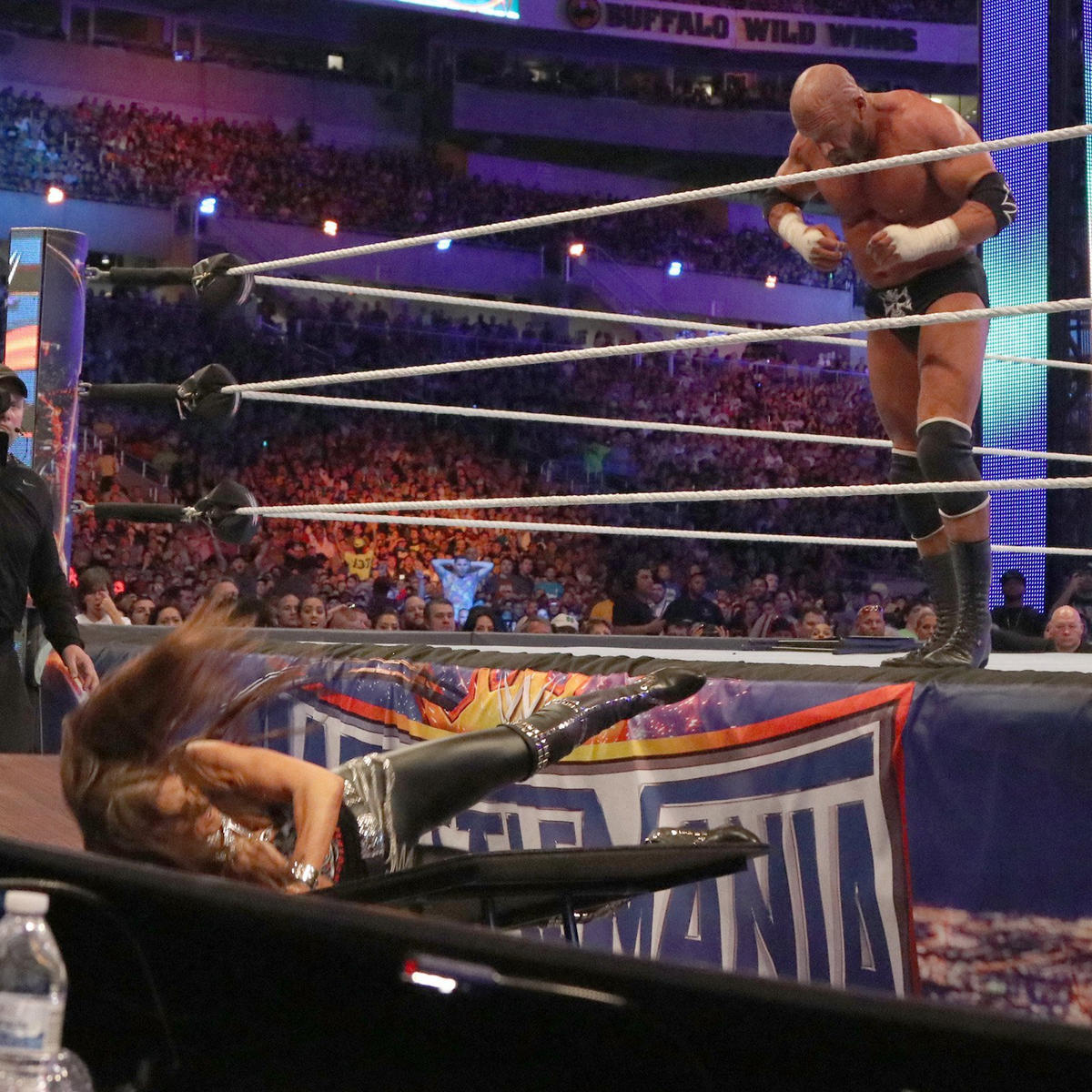Triple H inadvertently collides with Stephanie, sending her crashing through a table.