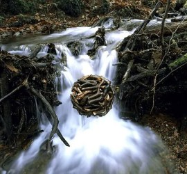 art in nature image of ball made from twigs over waterfall