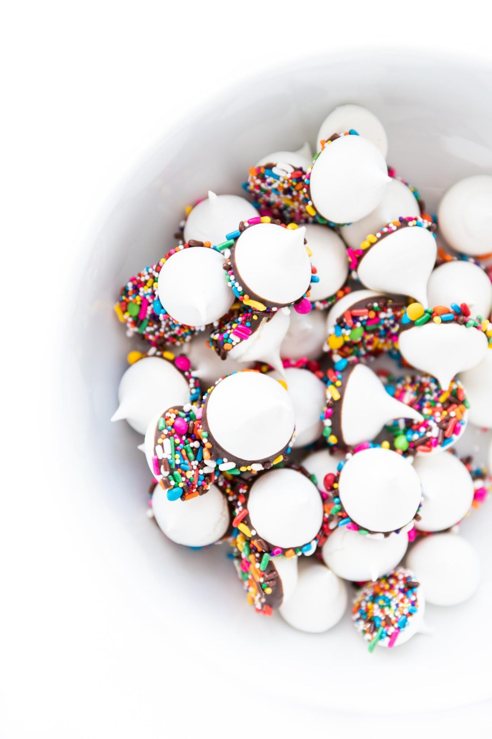 Confetti Meringue Kisses! Light crunch meringue dipped in chocolate and colorful sprinkles! A fun dessert that can be left out at parties and made ahead of time.