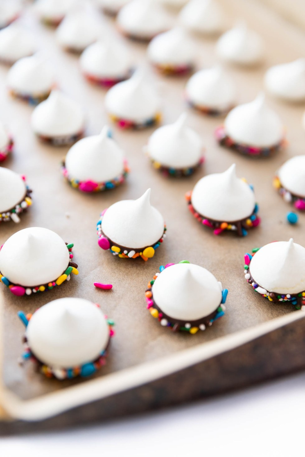 White meringues with halos of chocolate and colorful sprinkles sitting on parchment paper.