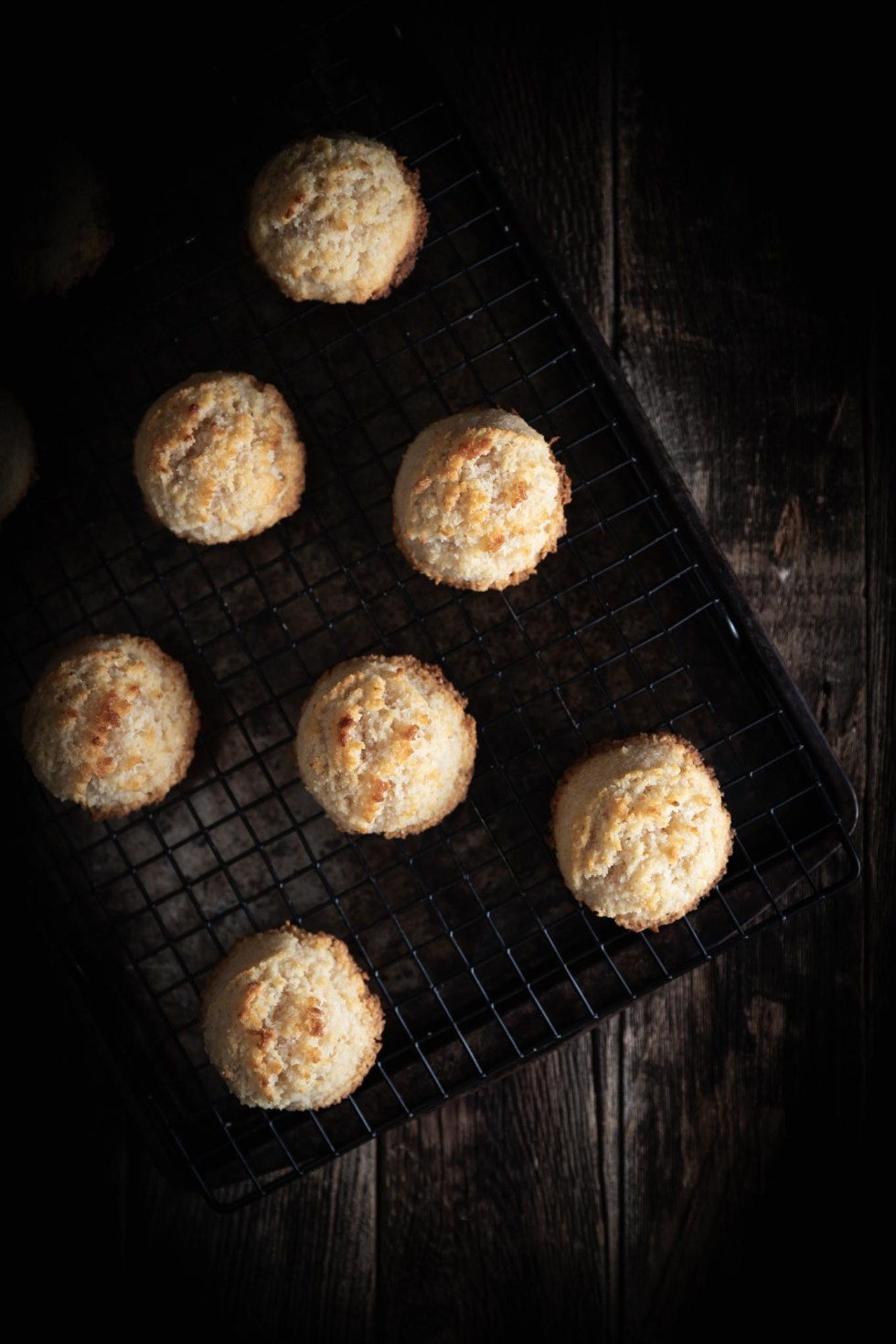 Overhead view of golden-brown coconut macaroons on a black cooling rack.