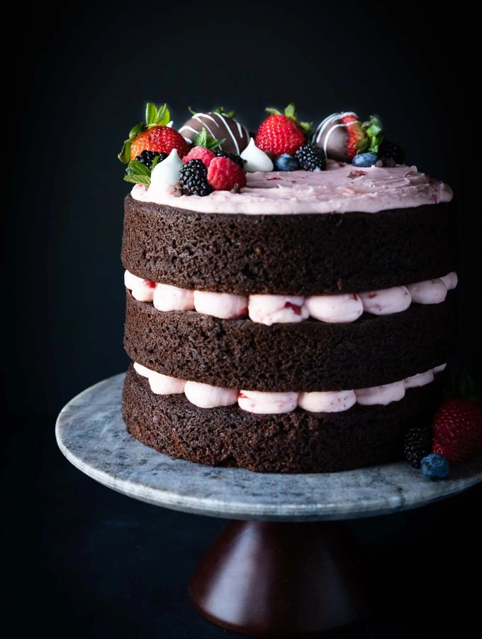 A rich, chocolate cake with fresh strawberry buttercream and topped with chocolate covered strawberries and mini meringues! Wedding cake or birthday cake, this is my go-to chocolate cake!