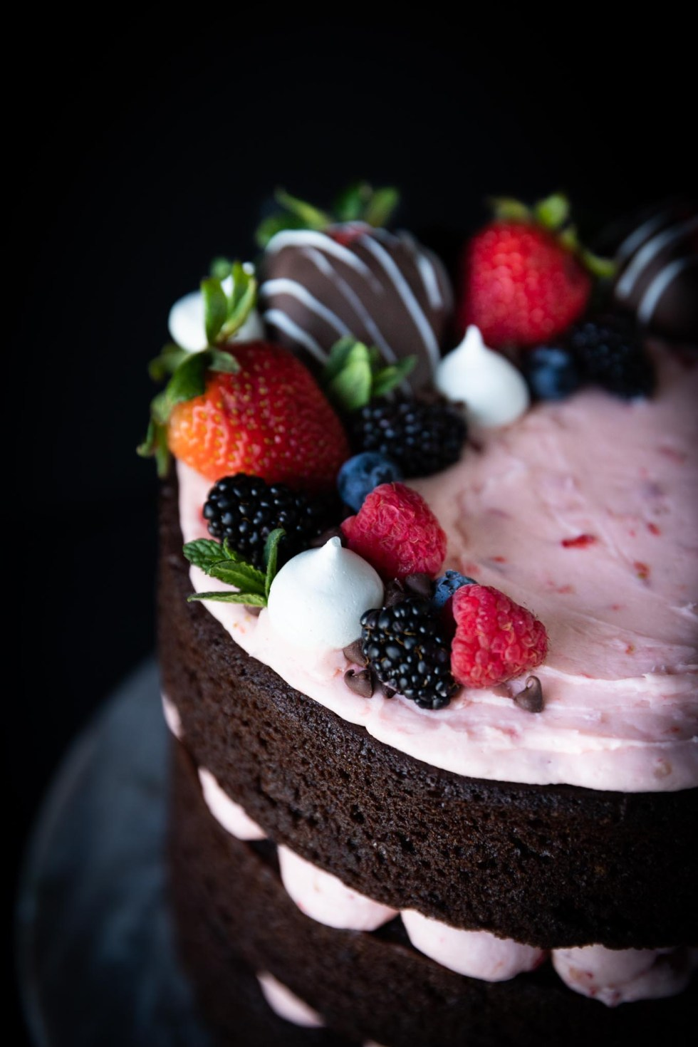 Close-up of berries, mini meringues, and chocolate covered strawberries on top of a bed of strawberry buttercream.