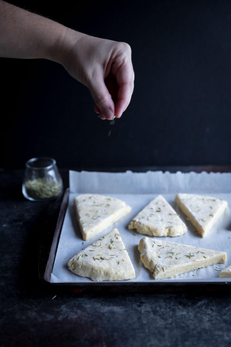 Sprinkling rosemary over scone dough triangles.