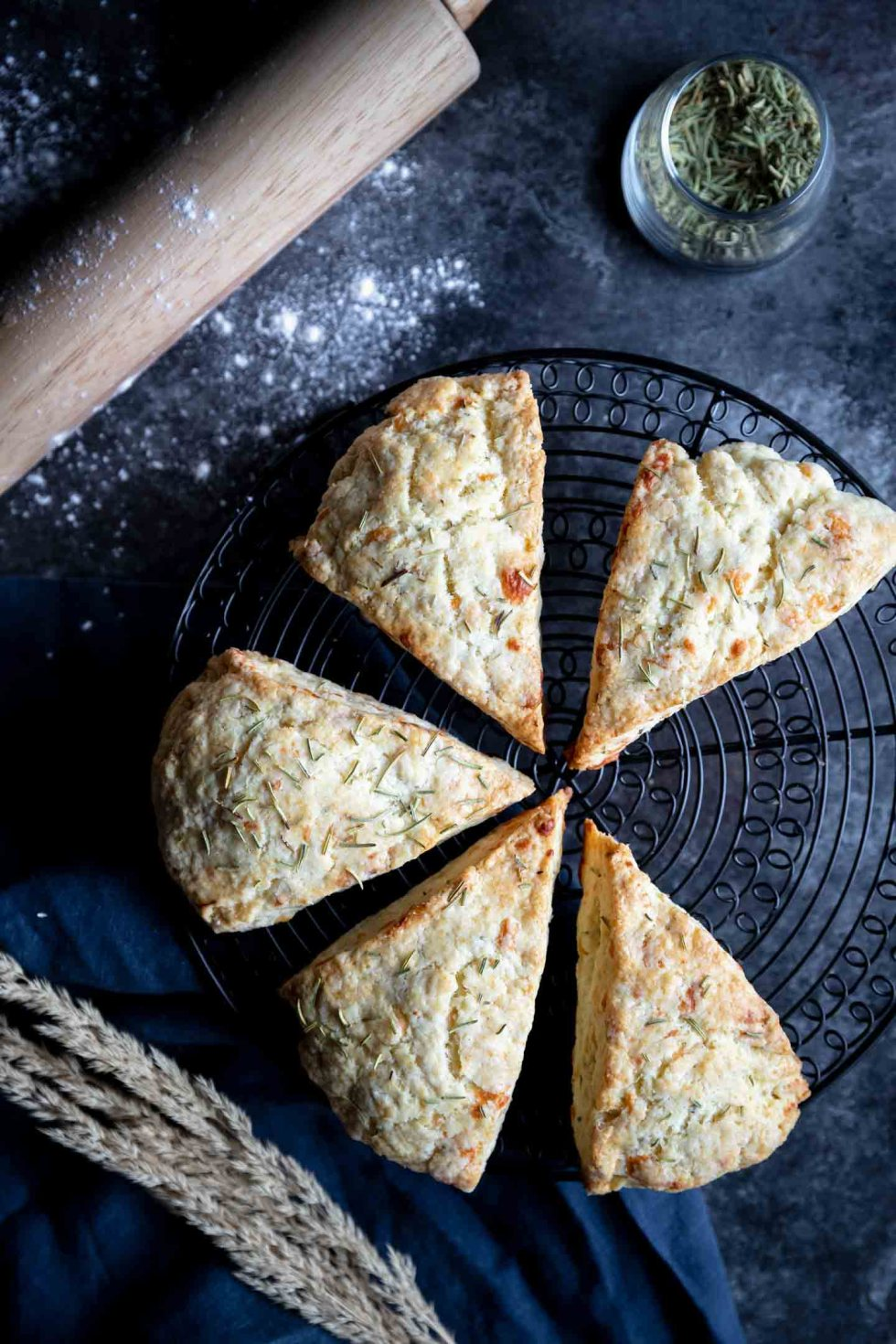 Browned rosemary parmesan scones on a black cooling rack.
