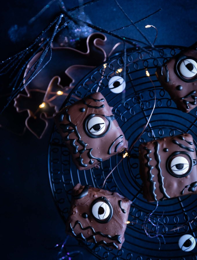 Brownies decorated like Hocus Pocus spellbooks cooling on a black wire rack.