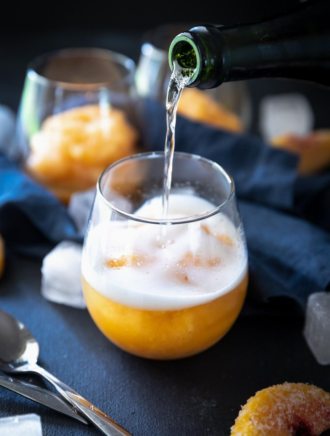 Pouring champagne over frozen peach slushie
