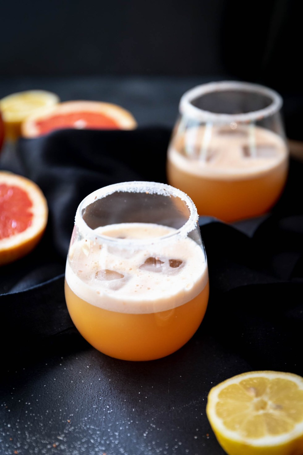 Dark and moody photograph of two stemless wine glasses filled with grapefruit margaritas