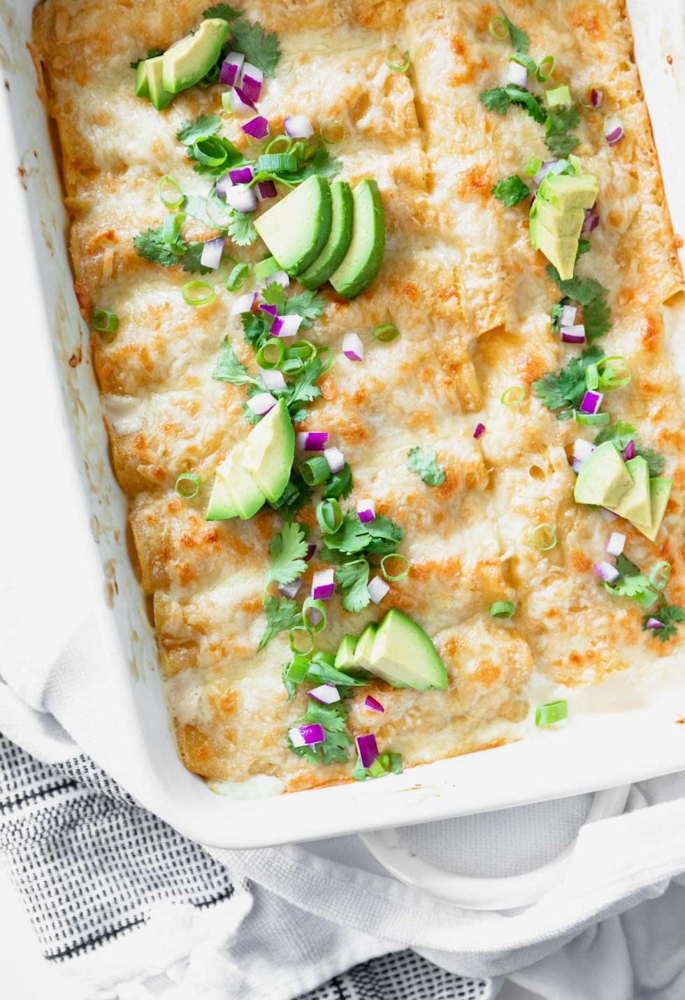 Overhead shot of white chicken enchiladas with avocado and cilantro