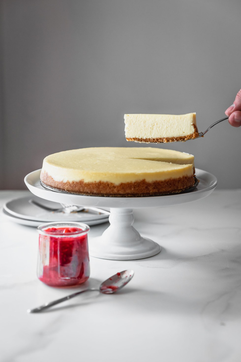 Slice of cheesecake being lifted off the cake stand