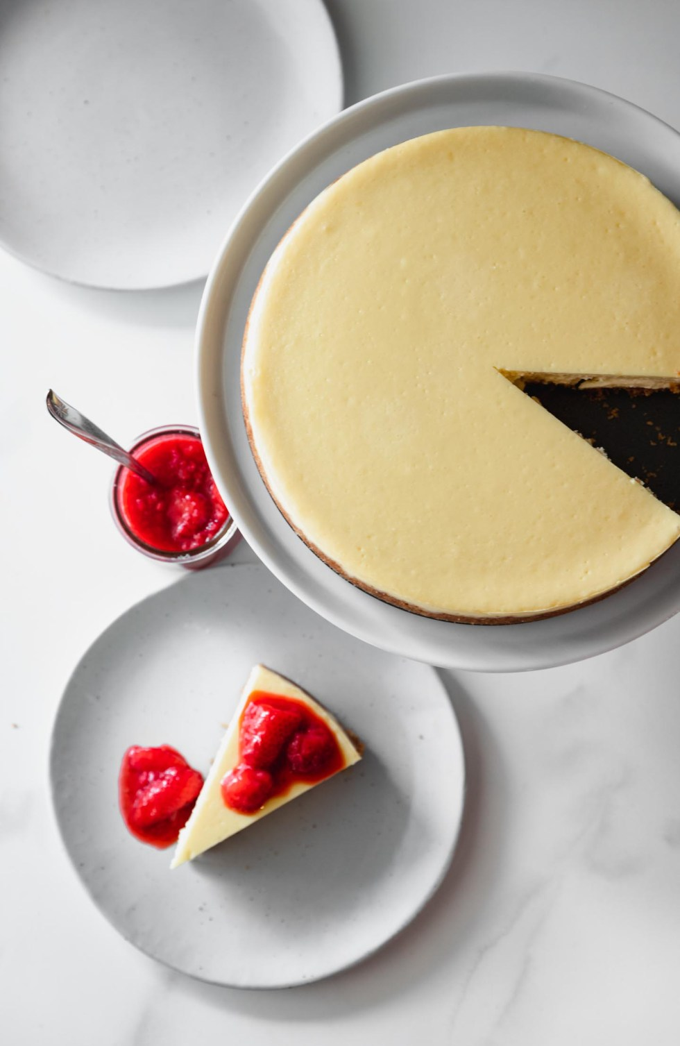 Overhead view of classic cheesecake with one slice removed to a small plate.