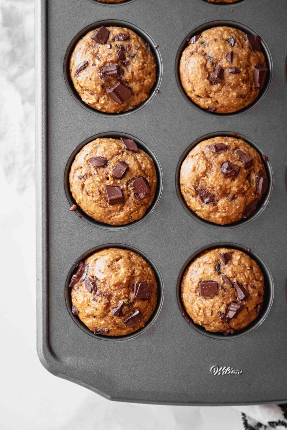 Overhead view of pumpkin muffins a a 12-cup gray muffin tin
