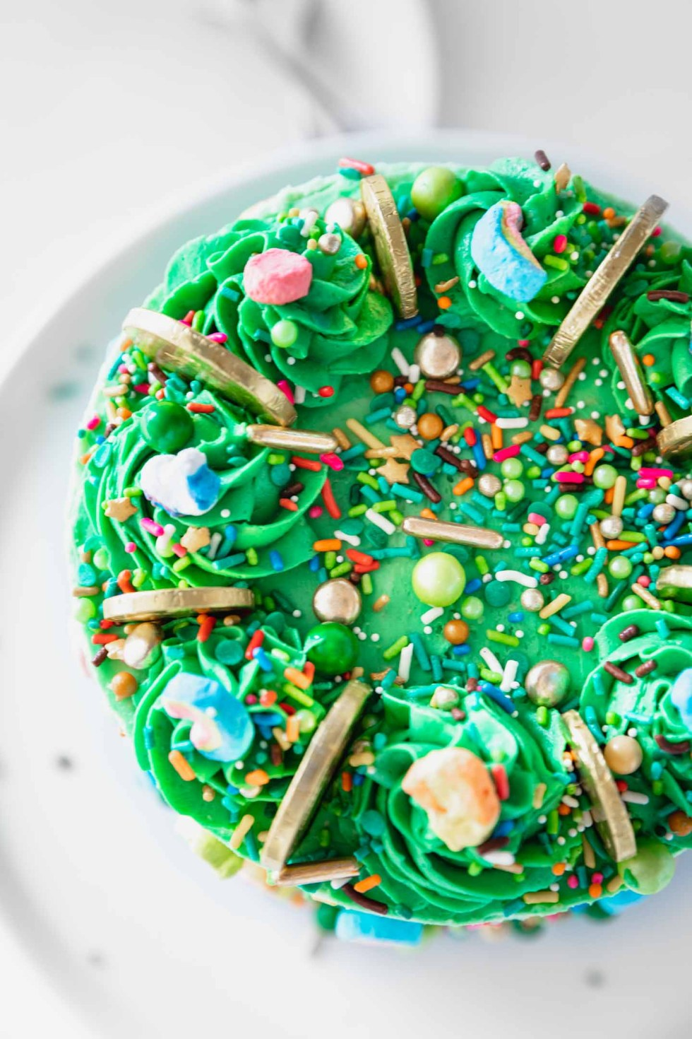 Overhead view of cake top with buttercream swirls and St. Patrick's day sprinkles and lucky charms marshmallows