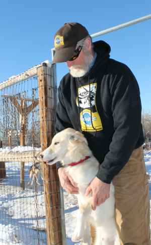 Jerry Bath holds one of his racing dogs. Bath, a Lander musher, started sled dog racing as a way to pass the winter months and work with animals. (WYOFILE PHOTO BY Kelsey Dayton)