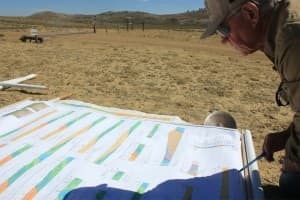Jay Lillegraven inspects a map of the Medicine Bow basin he has been studying ahead of DKRW Energy's development on the territory. (Allen Best/WyoFile — click to view)