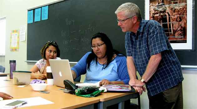 Daniel Fee discusses a final exam essay with (l. to r.) Benni Roberts, 31, a paraprofessional at Fort Washakie School, and Rory Tendore, 34, after-school program coordinator and administrative assistant to the principal at Fort Washakie School. (Ron Feemster/WyoFile — click to view)