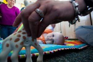 Michelle Carr holds 7-month-old Bridget's attention with Sophie the giraffe. Bridget hones her receptive language skills and exercises her largest muscles as she stretches to reach Sophie. Bus driver Mary Stevens helps out with some of the children.