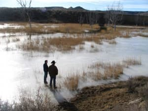 In this file photo from 2006, landowners observed a low-lying grazing area that was flooded and frozen with water discharged from coal-bed methane gas wells in the Powder River Basin. (Dustin Bleizeffer/WyoFile — click to enlarge)