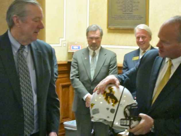 Gov. Matt Mead hands a commemorative Wyoming Cowboys football helmet to Halliburton CEO David Lesar. UW engineering task force member Tom Botts (second from left) and UW Foundation president Ben Blalock stand in the background. (WyoFile/Gregory Nickerson — click to enlarge)