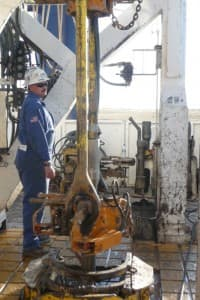 """This worker helped with the operation of Ensign's automated """"iron derrick hand"""" rig west of Casper in 2009. (Dustin Bleizeffer/WyoFile — click to enlarge)"""