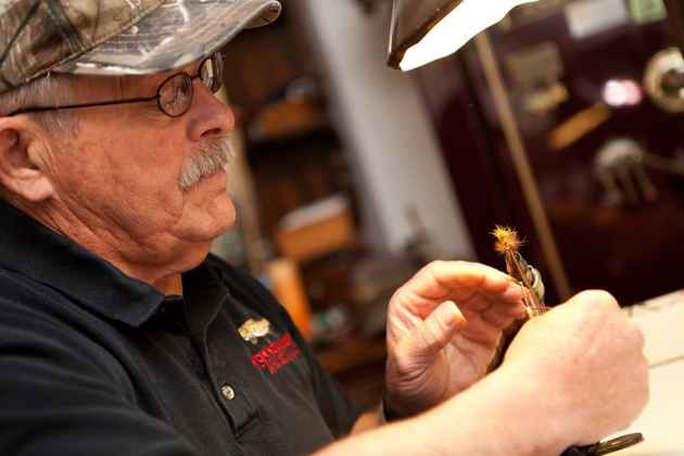 """Chuck McCall of Cheyenne is a fly-tier whose work is part of the """"Art of the Hunt"""" exhibit in Cheyenne. (Photo by Peter Gibbons - click to enlarge)"""