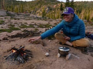 The author adds a stick to the fire while waiting for dinner to cook. (emilene Ostlind - click to enlarge)