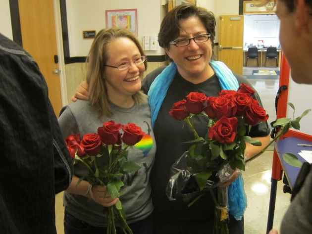 Bonnie Robinson (left) and Anne Guzzo brought roses for the first couple to apply for a marriage license in Laramie, Wyoming. They were among the plaintiffs in the federal court case Guzzo. V. Mead. (WyoFile/Gregory Nickerson — click to enlarge)