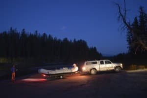 Unloading the raft at Pacific Creek in the glow of tail lights. (photo by Emilene  Ostlind - click to enlarge)