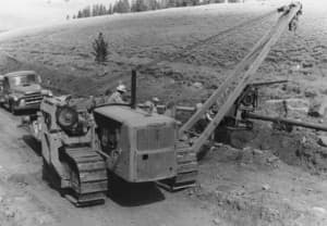 Workers use a tractor and side boom to lay pipe along a roadway, 1960s. (Casper College Western History Center. - click to enlarge)