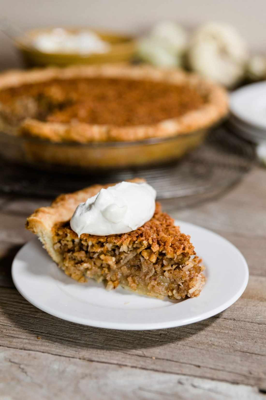 Slice of oatmeal nut pie sitting on white plate with whipped cream on top with rest of pie sitting on wire cooling rack in background along with white pumpkin and extra plates on a wood plank surface