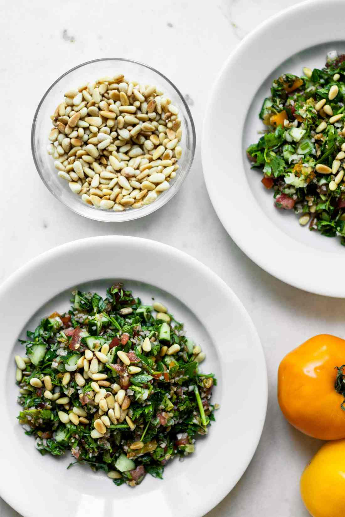Top down view of two bowls full of tabbouleh topped with pine nuts with tomatoes and bowl of pine nuts on a marble surface