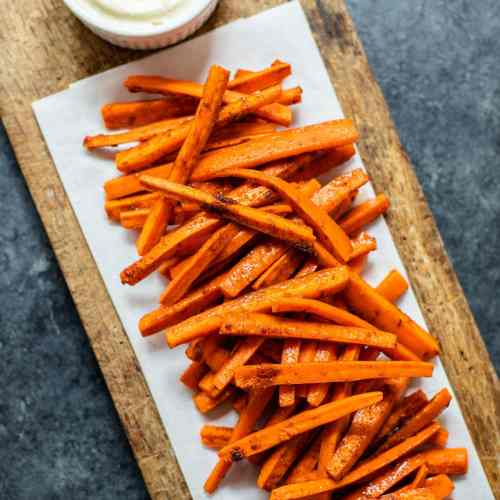 Orange harissa roasted carrots piled on a piece of parchment on a brown cutting board with bowl of garlic lemon aioli all on gray concrete surface