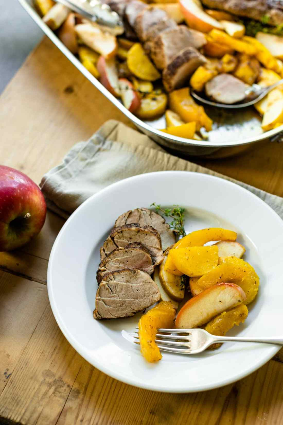 Roasted pork tenderloin with roasted apples and squash on white plate sitting on wood board with extra pan of meal in background all on gray slate surface