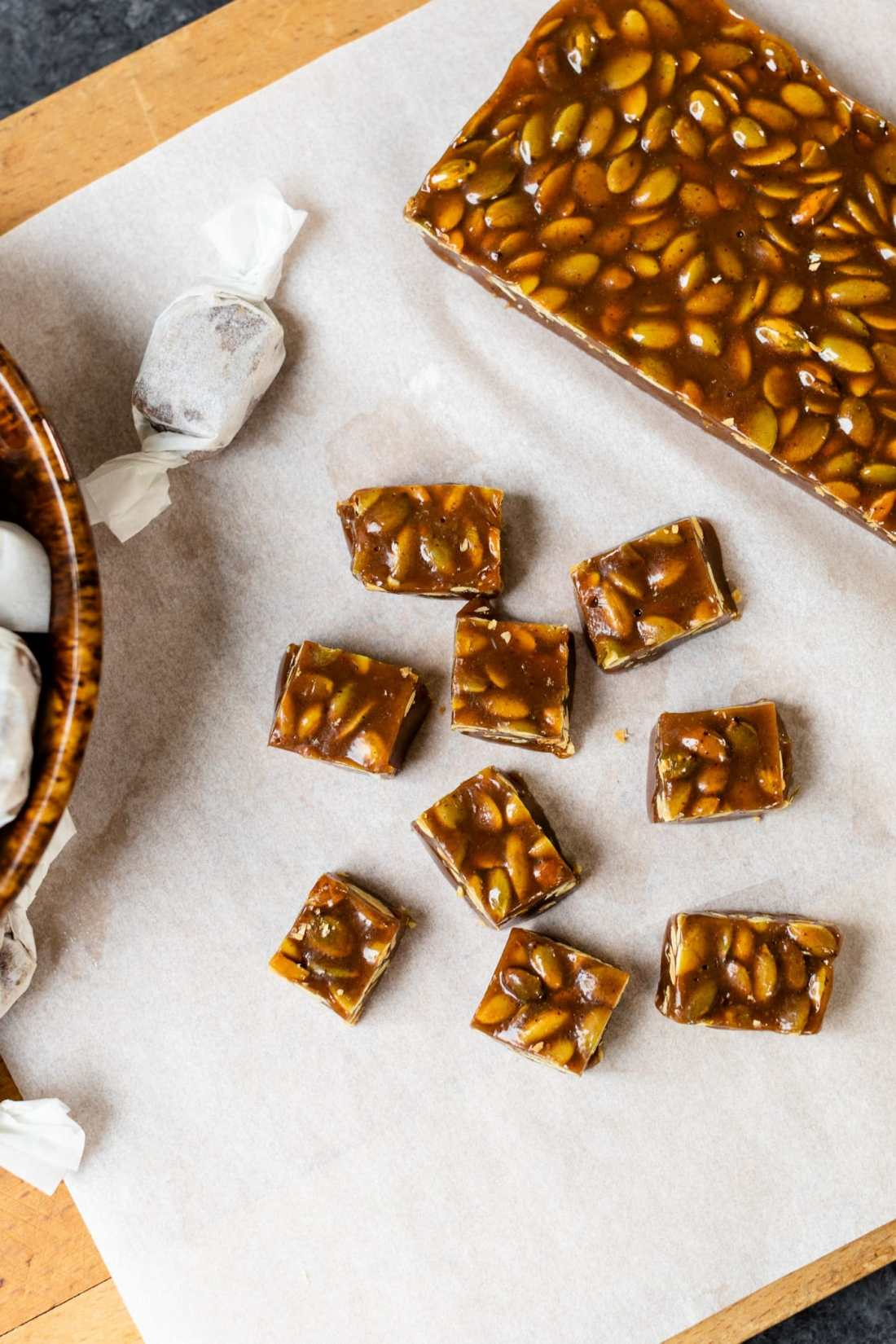Top down view of pumpkin spice caramels sitting on white parchment on board with bowl containing wrapped caramels all on gray slate surface