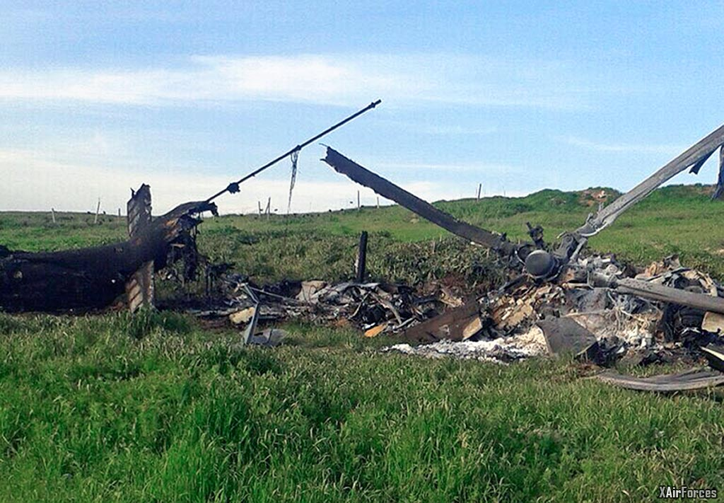 """Remains of a downed Azerbaijani forces helicopter lies in a field in the separatist Nagorno-Karabakh region, on Saturday, April 2, 2016. In a statement, Azerbaijan's Defense Ministry said 12 of its soldiers """"became shards"""" (Muslim martyrs) and said one of its helicopters was shot down. At least 30 soldiers and a boy were reported killed as heavy fighting erupted Saturday between Armenian and Azerbaijani forces over the separatist region of Nagorno-Karabakh. (AP Photo)"""