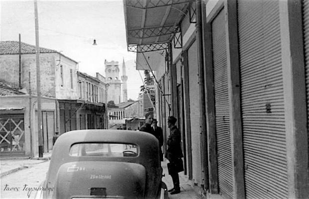 """Η οδός βασ. Κωνσταντίνου . Αριστερά διακρίνεται το κατάστημα με τα """"Χ"""" στα τζάμια ειναι στην γωνία με την οδο Κονίτσης . Δεξιά Βούλγαροι αξιωματικοί. Η φώτο ειναι το 1941."""