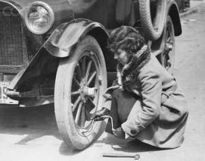 Young Woman Fixing Flat On Old Car.