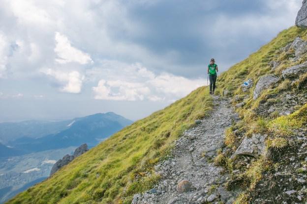 אישה מטיילת ועולה בשביל על הר ירוק עם נוף מדהים