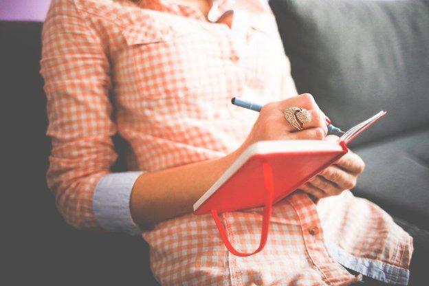 אישה יושבת וכותבת במחברת