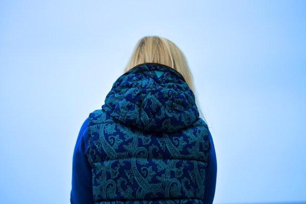 אישה מסתכלת לאופק רחוק עם מעיל שהגב למצלמה