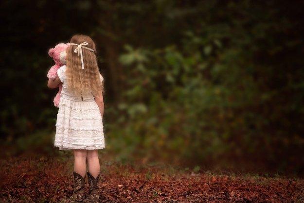ילדה עם דובון שמסתכלת ליער
