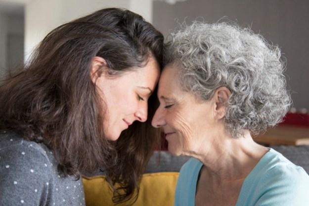 אישה מבוגרת וצעירה שמות מצח למצח במבט טוב ואוהב