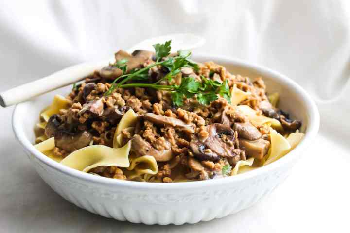 vegetarian stroganoff in a white bowl with a wooden spoon